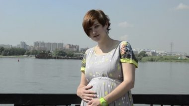 Pregnant beautiful young woman by embankment, near the river — Stock Video