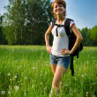 Happy woman turist in a summer field with backpack — Stock Photo