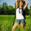 Happy woman turist in a summer field with backpack and bike — Stock Photo