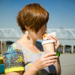 Pregnant woman on the waterfront eating sandwich and drinking te — Stock Photo