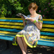 Pregnant woman reading magazine on the bench — Stock Photo