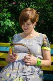 Těhotná dívka sedící na lavičce se sluchátky v parku — Stock fotografie