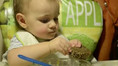 Baby girl is eating porridge — Vídeo de stock