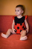 Baby in ladybird costume plays on the couch — Stock Photo