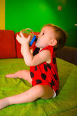 Baby in ladybird costume drinks from bottle on the couch — Stock Photo