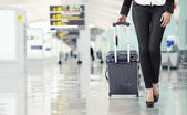 Young woman pulling luggage at the airport, close up sexy legs — Stock Photo