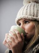 Beautiful young girl drinking coffee or tea — Stock Photo