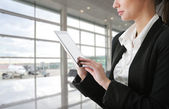 Businesswoman using tablet computer at departure lounge — Stock Photo