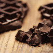 Pieces of dark chocolate  on a wooden background — Stock Photo