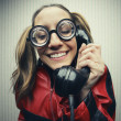 Nerdy woman speaking on a black rotary vintage phone — Stock Photo #21383313