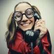 Nerdy woman speaking on a black rotary vintage phone - Stock Photo
