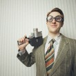 Nerdy businessman with old fashioned cine camera — Stock Photo #22531069