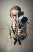 Nerdy young man with movie camera — Stock Photo