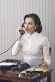 Woman talking on phone at desk — Stock Photo