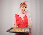 Retro housewife sneaking cookies — Stock Photo