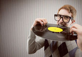 Nerd student angry, biting a vinyl record — Stock Photo