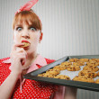 Retro housewife sneaking cookies — Stock Photo