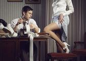 Молодая сексуальная женщина показывает ногу для делового человека — Стоковое фото