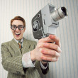 Nerdy young man using old fashioned cine camera — Stock Photo