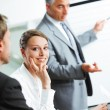 Smiling woman sitting at a business meeting with colleagues — Stock Photo #25944673