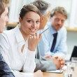 Smiling woman sitting at a business meeting with colleagues — Stock Photo #25957827