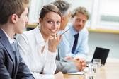 Mujer sonriente sentada en una reunión de negocios con colegas — Foto de Stock