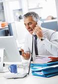 强调业务名男子大喊着办公室里的电话 — 图库照片