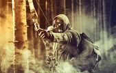 A male bow hunter wearing gas mask — Stock Photo