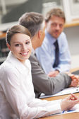 Smiling woman sitting at a business meeting with colleagues — Stock Photo