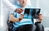 Doctor showing X-ray to patient — Stock Photo
