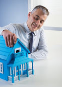 Real estate agent with model house — Stock Photo