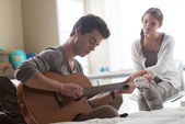 Romantic boy playing guitar for her girlfriend — Stock Photo