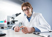 Chemical laboratory technician holding magnifier — Stockfoto