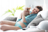 Girl playing with dog on sofa — Stock Photo