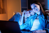 GIrlfriends on a sofa with laptop — Stock Photo