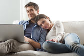 Couple relaxing on sofa with laptop — Stock Photo