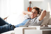 Guy with headphones on sofa — Stock Photo