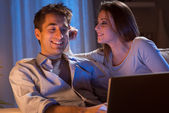 Young couple at home with laptop — Stock Photo