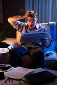 Businessman reading newspaper late at night — Stock Photo