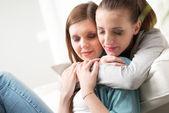 Girlfriends hugging on sofa — Stock Photo