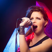 Pop star singing on stage — Stock Photo
