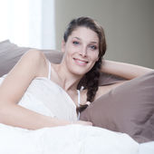 Woman smiling while lying in bed — Stock Photo