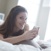 Relaxed woman at home reading a text message in her bright bedroom — Stock Photo
