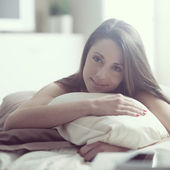Woman smiling while lying in bed — Foto Stock