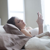 Young woman lying on the bed at home and receiving a text — Stock Photo