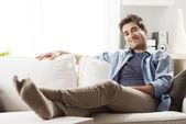 Młody człowiek na kanapie — Zdjęcie stockowe