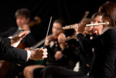 Conductor directing symphony orchestra — Stock Photo