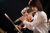 Female flutist with orchestra on stage — Stock Photo