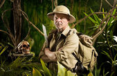 Adventurer with colonial style survival equipment in the jungle with skull. — Stock Photo