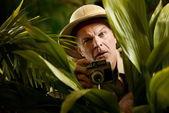 Explorer photographer hiding in vegetation — Stock Photo